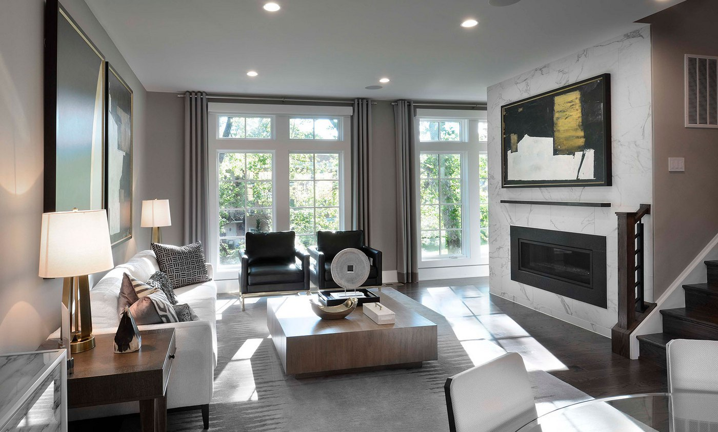 The Avalon's spacious living room features floor-to-ceiling windows and an elegant fireplace